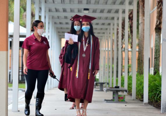 Recent graduates holding diplomas