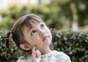 Little girl looks to sky and ponders